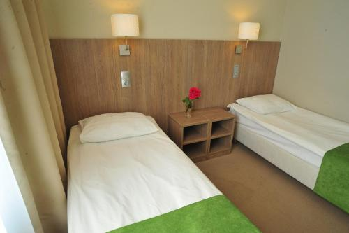 A bed or beds in a room at Yunost Hotel