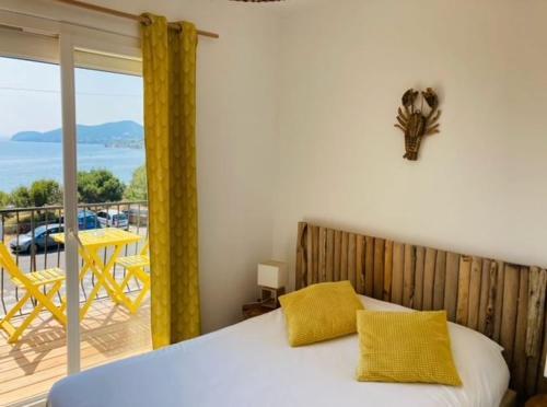 A bed or beds in a room at Hôtel Almanarre Plage - Hôtel Eco-Responsable