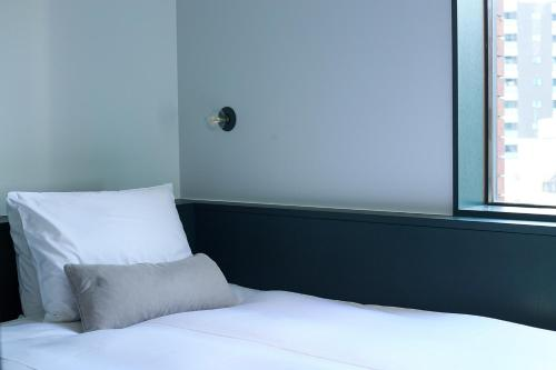 A bed or beds in a room at DDD HOTEL