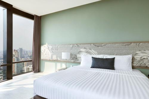 A bed or beds in a room at The Quarter Ari by UHG