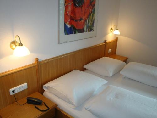 A bed or beds in a room at Hotel-Garni Austria
