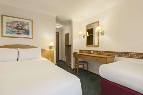 A bed or beds in a room at Days Inn Hotel Leicester