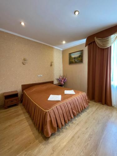 A bed or beds in a room at Gusarskiy Hotel and Apartment