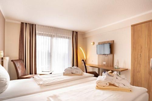 Ein Bett oder Betten in einem Zimmer der Unterkunft Aqualux Wellness- & Tagungshotel