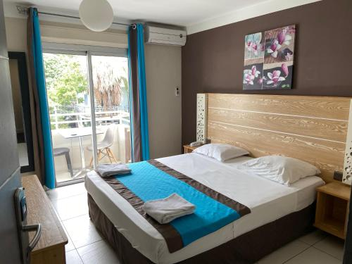 A bed or beds in a room at Hôtel Select - Réunion