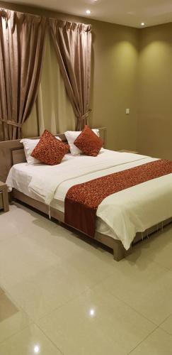 Cama ou camas em um quarto em Qasr Wasan Furnished Apartments - Al Aziziyah