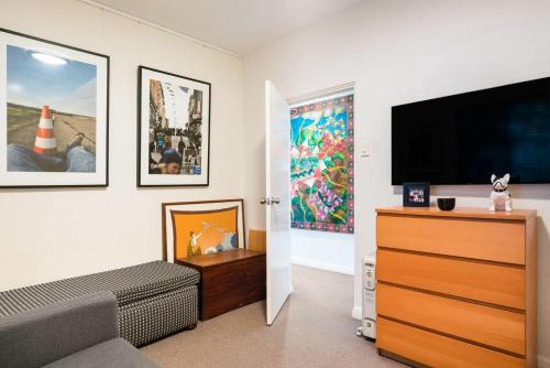 A television and/or entertainment center at Waterfront Apartment Brimming with Inspirational Artwork