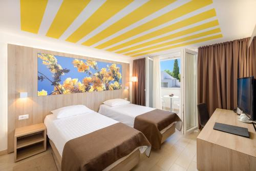 A bed or beds in a room at Medora Auri Family Beach Resort