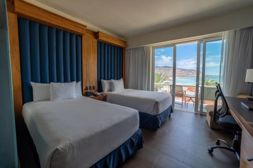 A bed or beds in a room at Costa Baja Resort & Spa