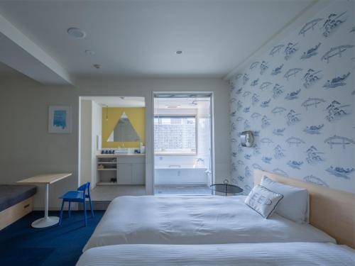 A bed or beds in a room at The Share Hotels Lyuro Tokyo Kiyosumi