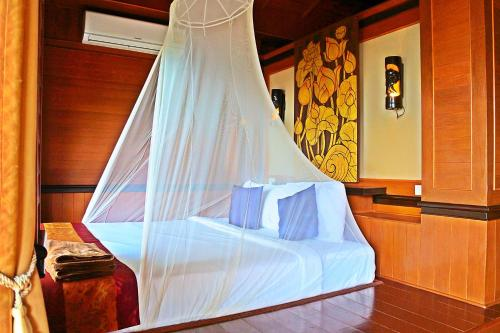A bed or beds in a room at Baan Laanta Resort & Spa
