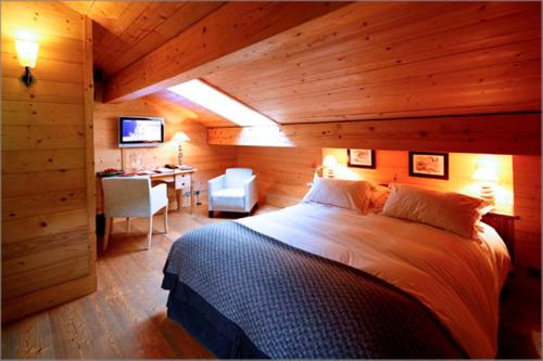 A bed or beds in a room at La Ferme du Chozal, The Originals Relais