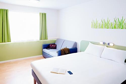 A bed or beds in a room at ibis Budget Warrington Lymm Services