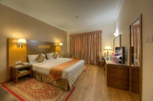 Säng eller sängar i ett rum på Fortune Pearl Hotel