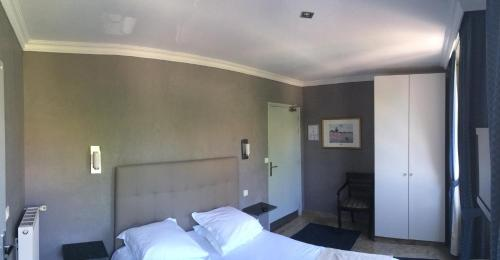 A bed or beds in a room at Hôtel Saint Alban