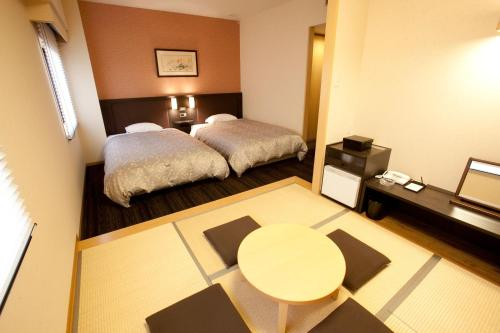 A bed or beds in a room at Toyama Manten Hotel