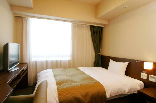 A bed or beds in a room at Dormy Inn Kumamoto Natural Hot Spring