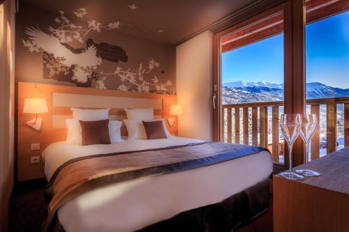 A bed or beds in a room at Le Grand Aigle Hotel & Spa****