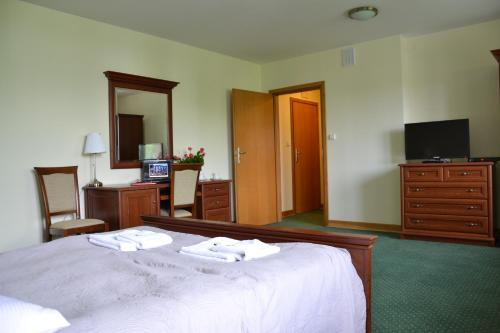 A bed or beds in a room at Hotel Łazienkowski