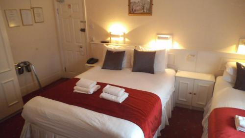 A bed or beds in a room at Arran House Hotel