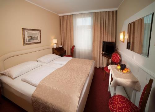 Ein Bett oder Betten in einem Zimmer der Unterkunft Hotel Vier Jahreszeiten Salzburg