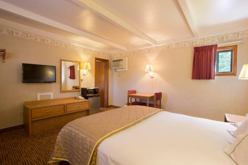 A bed or beds in a room at Glenwood Springs Cedar Lodge