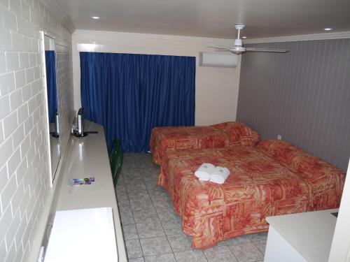 A bed or beds in a room at Emu Park Motel