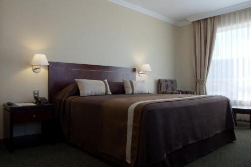 A bed or beds in a room at Hotel Diego de Almagro Temuco