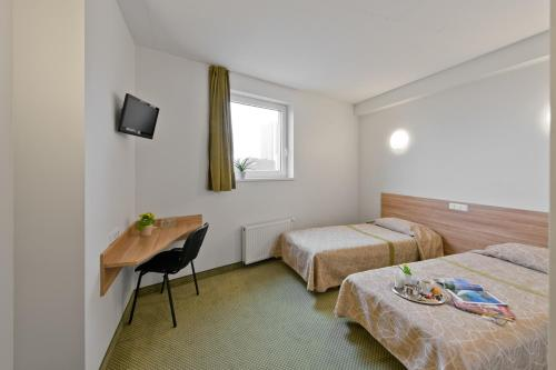 A bed or beds in a room at Green Vilnius Hotel