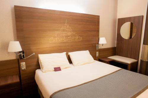 A bed or beds in a room at Mercure Mont Saint Michel
