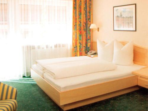 A bed or beds in a room at Hotel Garni Angelika