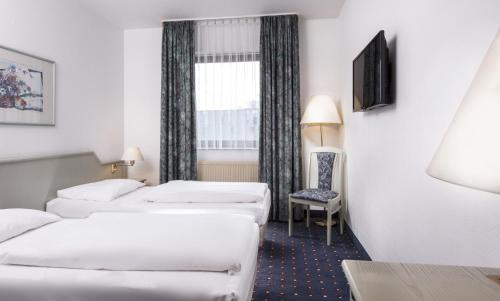 A bed or beds in a room at Wyndham Garden Duesseldorf Mettmann