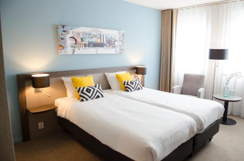 A bed or beds in a room at Fletcher Hotel-Restaurant Weert (Former Golden Tulip Weert)