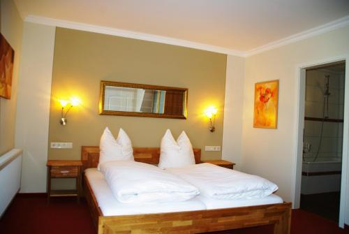 A bed or beds in a room at Landhotel Heidekrug