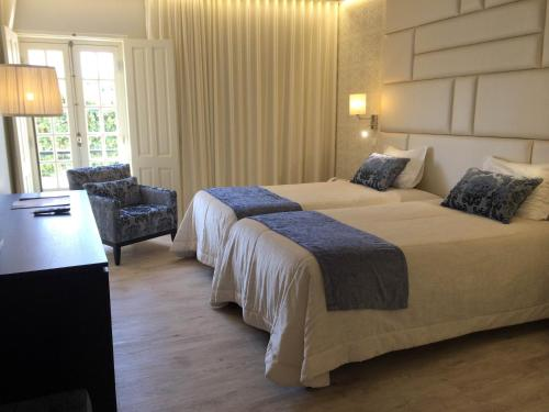 A bed or beds in a room at Josefa D`Obidos Hotel