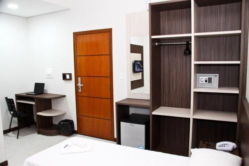 Uma TV ou centro de entretenimento em Miotto Executive Hotel
