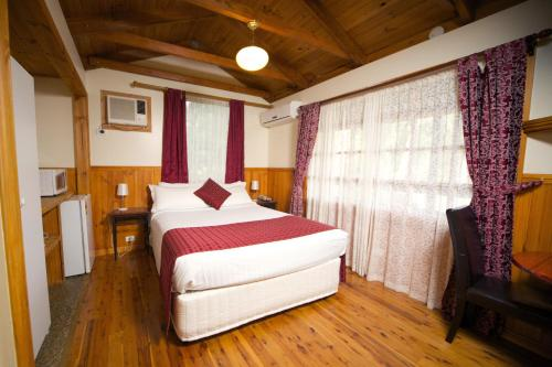A bed or beds in a room at Sanctuary House Resort Motel