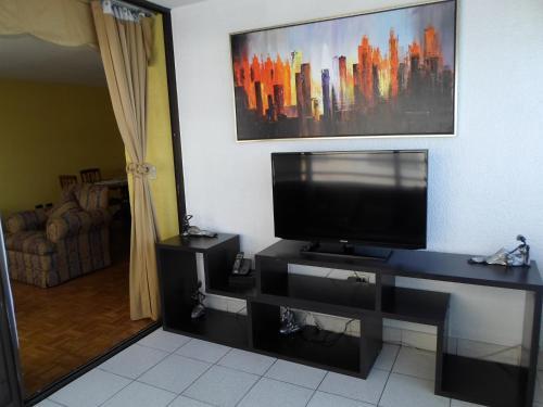Una televisión o centro de entretenimiento en Departamento Amoblado Av. Grecia