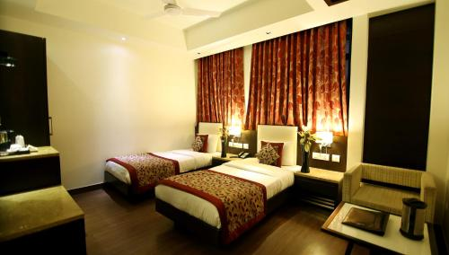 A bed or beds in a room at The Prime Balaji Deluxe @ New Delhi Railway Station