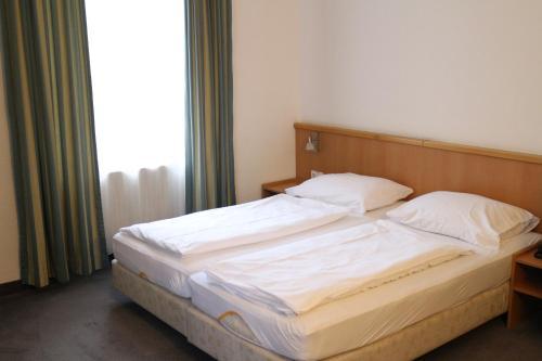Кровать или кровати в номере Hotel Kolbeck am Columbusplatz