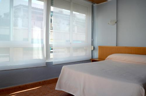 A bed or beds in a room at Hotel Cervantes