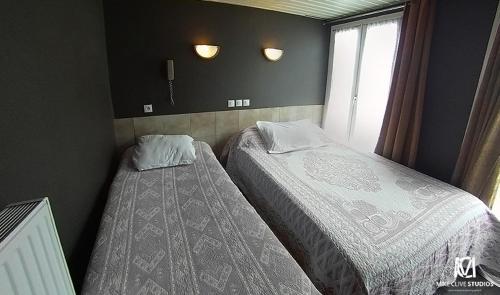 A bed or beds in a room at Hôtel Jarry Confort