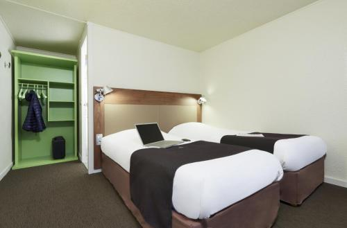 A bed or beds in a room at Campanile Lille Sud - CHR
