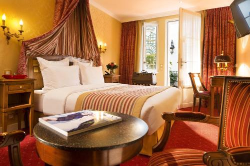 A bed or beds in a room at Hôtel de Varenne