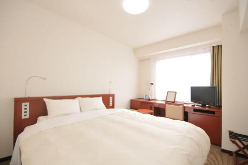 A bed or beds in a room at Grand Park Hotel Odate