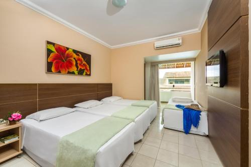 A bed or beds in a room at Transoceanico Praia Hotel