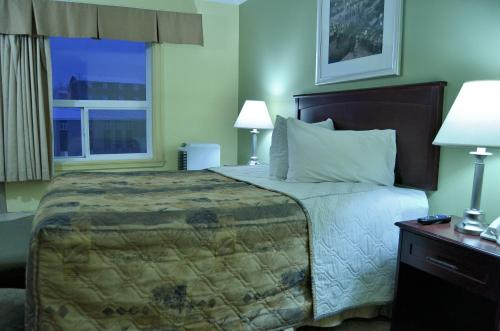 A bed or beds in a room at Nova Inn Inuvik