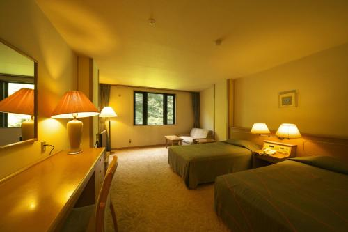 A bed or beds in a room at Hodakaso Yamano Hotel