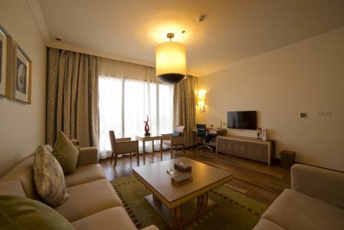 Uma área de estar em Golden Tulip Dammam Corniche Hotel
