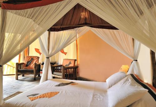 A bed or beds in a room at Tanganyika Blue Bay Resort